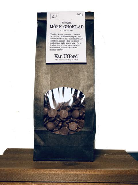 Svart påse i papper med fönster där chokladknappar i mörk choklad syns. 300g.