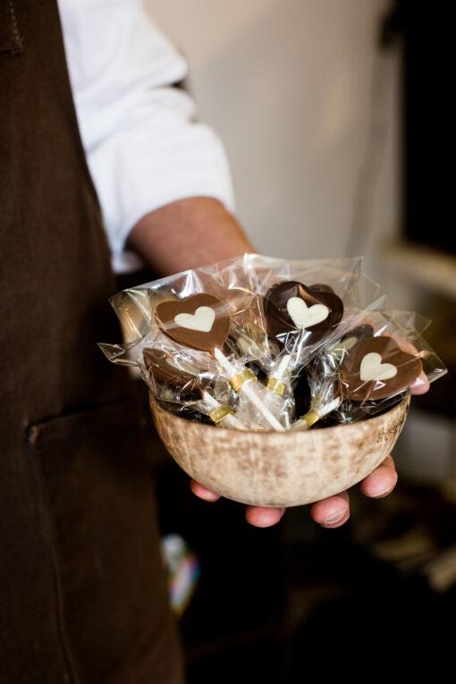 Kokosskål med hjärteklubbor av mjölkchoklad och vit choklad är en fin present som finns i vår webbshop och fabriksbutik.