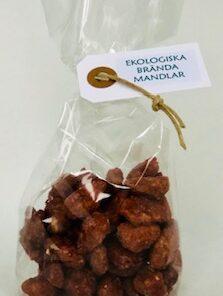 Cellofanpåse med ekologiska brända mandlar. Hängetikett och knutet snöre.
