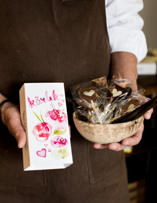 Händer som håller i en Kärlekspresent med illustration av Matilda Svensson och hjärtekubbor i choklad som ligger i en kokosskål