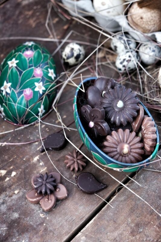 Vackert grönt Fabergéägg i plåt fyllt med blommor av mörk choklad och mjölkchoklad med pastellfärgad pistill av chokladkonfetti. Ekologiskt och handgjord.