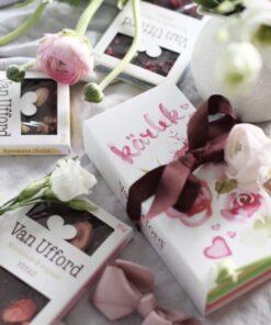 Van Ufford presentomslag Kärlek med tre chokladkor i och tre chokadkakor runt om. Vacker vinröd rosett knuten om presenten.