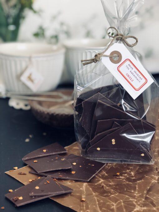 Cellofanpåse med bräck av mörk choklad med chili. Knutet med snöre och hängetikett.
