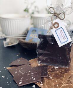 Cellofanpåse med bräck av mörk choklad med havssalt. Snöre och hängetikett.