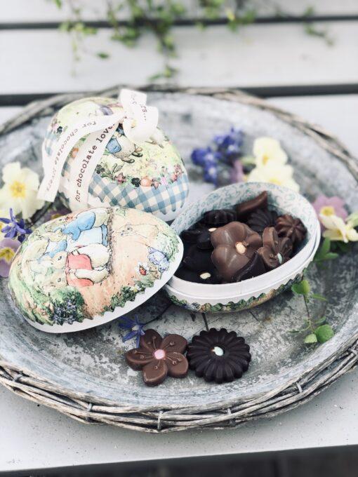 Påskägg i papp och med motiv av Beatrice Potter fyllt med handgjorda chokladblommor i mörk choklad och mjölkchoklad.