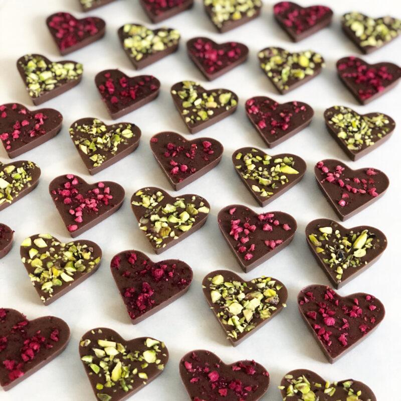 Chokladhjärtan på plåt. Hjärtan med gröna pistagenötter och hallon i rader.