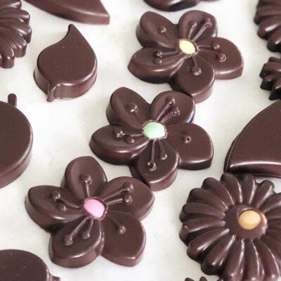 Närbild på chokladblommor i mörk choklad med pastellfärgad prick i mitten.
