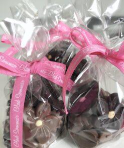 Transparent påse med blommor gjorda i mörk choklad och mjölkchoklad med en pastellfärgad prick i mitten. Rosa band med texten Glad sommar!