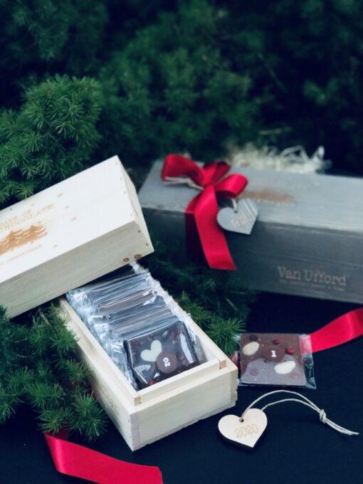 Chokladkalender i träask, grå eller trären med röda band och litet hjärta i trä som hänge.