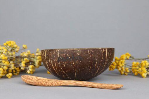 Kokosskål och sekd av kokosträ från Pandoo samt gula blommor som dekoration.