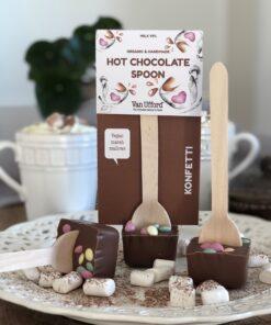 Hot chocolate spoon mjölkchoklad Konfetti med marshmallows och en kopp varm choklad i bakgrunden.