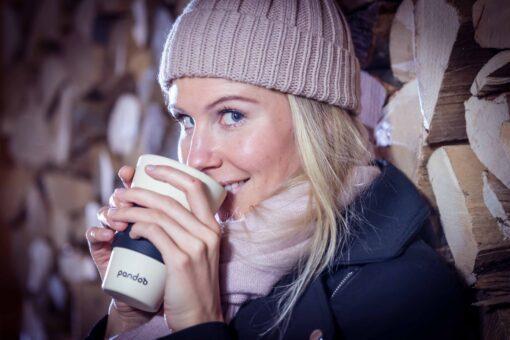 Ung tjej med vinterjacka och rosa mössa dricker någonting varmt ur krämvit åeranvändbar mugg med svart silikonvärmeskydd.