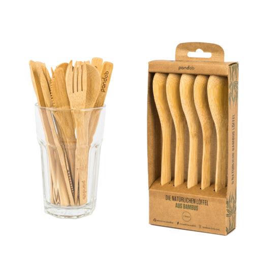 Skedar av bambu i brun pappersförpackning om fem skedar. Brevid ett dricksglas med skedar, gafflar och knivar av bambu.