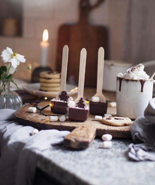 Stämningsfull bild med bord, tänt ljus och tre Hot chocolate spoons samt mugg med varm choklad och marshmallows