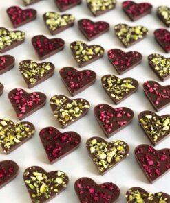 Plåt fylld med chokladhjärtan med hallon och pistagenöt ovanpå